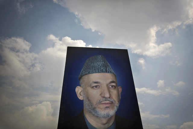 In this Saturday, March 29, 2014 photo, a giant picture of Afghan President Hamid Karzai is displayed on the parade ground of the Ministry of Defense in Kabul, Afghanistan. Karzai inherited a brok ...