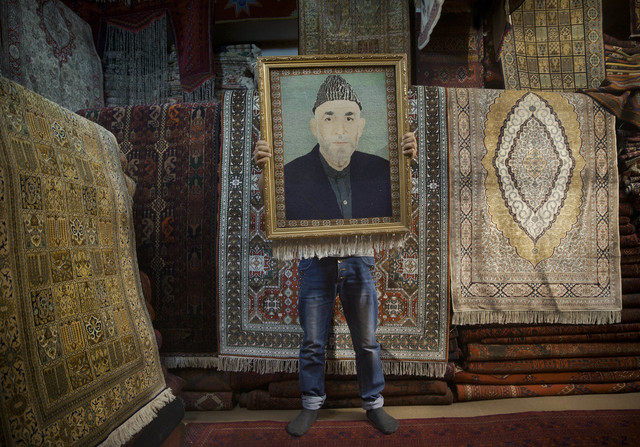An Afghan carpet seller holds up a framed carpet depicting Afghan President Hamid Karzai in his store in Kabul, Afghanistan, Sunday, March 30, 2014. Afghans go to the polls April 5, 2014 to choose ...