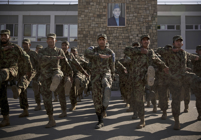 FILE - In this Nov. 26, 2013 file photo Afghan Army soldiers exercise under a picture of Afghanistan's President Hamid Karzai at a training facility in the outskirts of Kabul, Afghanistan. Afghans ...