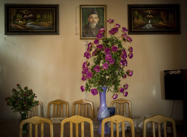 In this Saturday, March 29, 2014 photo a picture of Afghan President Hamid Karzai hangs on a wall in the main room of the district municipality in eastern Kabul. Afghans go to the polls April 5, 2 ...