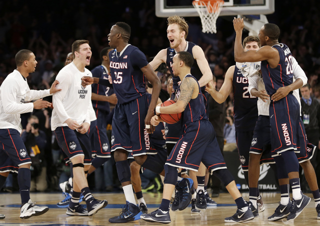 Connecticut players celebrate after beating Michigan State 60-54 in a regional final at the NCAA college basketball tournament, Sunday, March 30, 2014, in New York. (AP Photo/Seth Wenig)