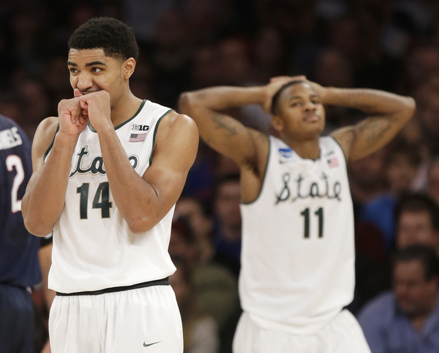 Michigan State's Gary Harris and Keith Appling react in the second half of a regional final against Connecticut at the NCAA college basketball tournament on Sunday, March 30, 2014, in New York. (A ...