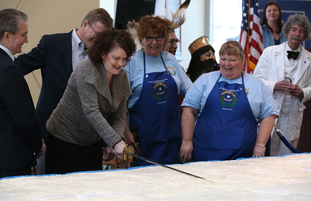 Nevada First lady Kathleen Sandoval uses a sword to cut into a 1,300 pound cake at the Battle Born Birthday Cake Celebration at the Carson Tahoe Regional Medical Center, in Carson City, Nev., on F ...