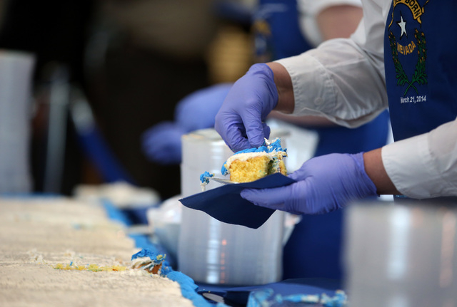 Volunteers serve up pieces of the 1,300 pound cake at the Battle Born Birthday Cake Celebration at the Carson Tahoe Regional Medical Center, in Carson City, Nev., on Friday, March 21, 2014. Volunt ...