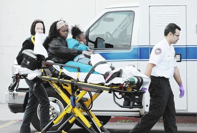 EMTs bring people to an ambulance at a Food4Less grocery store at Sahara Avenue and Eastern Avenue Saturday, March 1, 2014. Many we're injured when a woman in her 80's drove her truck into the sto ...