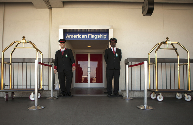 FILE - In this Thursday, March 14, 2013 file photo, American Airlines skycaps Alex Abel Gonzalez, left, and Frederick Pearson await outside the AA Flagship lounge at Los Angeles International Airp ...