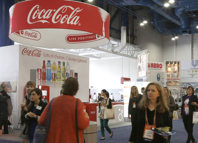 In this Oct. 21, 2013 photo, attendees at a conference for dietitians pass by a booth sponsored by Coca Cola, in Houston. As Americans struggle to improve their eating habits, big food companies a ...