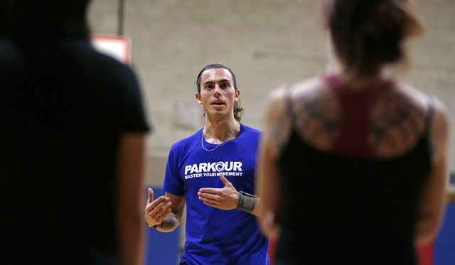 In this Wednesday, Jan. 29, 2014 photo, Blake Evitt, an instructor with Parkour Generations Americas, talks with his students during a Parkour training class in Brookline, Mass.  (AP Photo/Charles ...