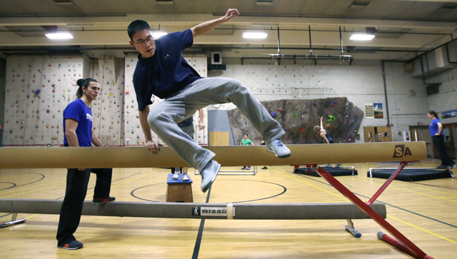 In this Wednesday, Jan. 29, 2014 photo, Michael Chung, of Brookline, Mass., leaps over a balance beam while running an obstacle course during a Parkour training class in Brookline. (AP Photo/Charl ...