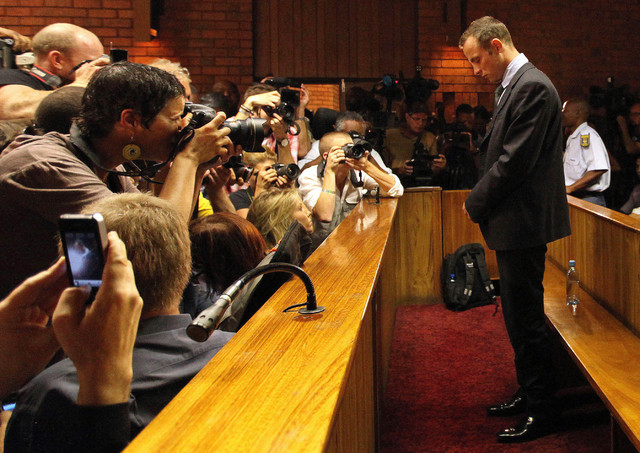 In this Wednesday, Feb. 20, 2013 file photo Olympic athlete Oscar Pistorius stands inside a court during his bail hearing at the magistrate court in Pretoria, South Africa. Pistorius will defend h ...