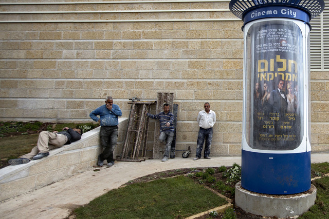 """I this Thursday, Feb. 27, 2014 photo, workers stands next to a movie poster for the movie """"American Hustle"""" translated to Hebrew as American Dream outside a cinema in Jerusalem. David O. ..."""