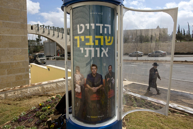 """In this Tursday, Feb. 27, 2014 photo, an ultra-Orthodox Jewish man walks past a movie poster for the movie """"That awkward moment"""" translated to Hebrew as """"The date that embarrassed m ..."""