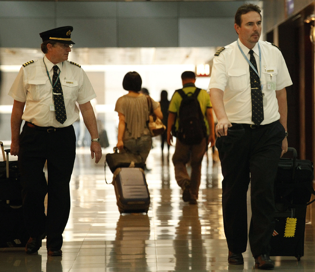 In this  Nov. 30, 2011 photo, two pilots from Cathay Pacific walk in the Hong Kong International Airport in Hong Kong.  The U.S. airline industry will need to hire 1,900 to 4,500 new pilots annual ...