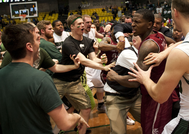 In this Thursday, Feb. 27, 2014 photo, New Mexico State's DK Eldridge, at right in red and white uniform, is held by security during  a brawl involving players and fans who came onto the court whe ...