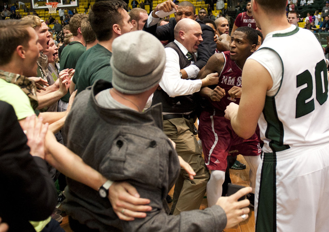 In this Thursday, Feb. 27, 2014 photo, New Mexico State's DK Eldridge, at right center in red and white uniform,  is controlled by security during a brawl involving players and fans who came onto  ...