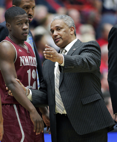 FILE - In this Dec. 11, 2013 file photo, New Mexico States' head coach Marvin Menzies, right, pulls K.C. Ross-Miller (12) aside and talks to him during a time-out in the second half against Arizon ...