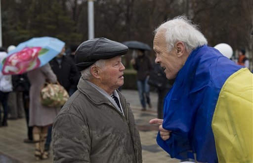 Two men talk during a rally against the breakup of the country in Simferopol, Ukraine on Friday. Ukraine lurched toward breakup Thursday as lawmakers in Crimea unanimously declared they wanted to  ...