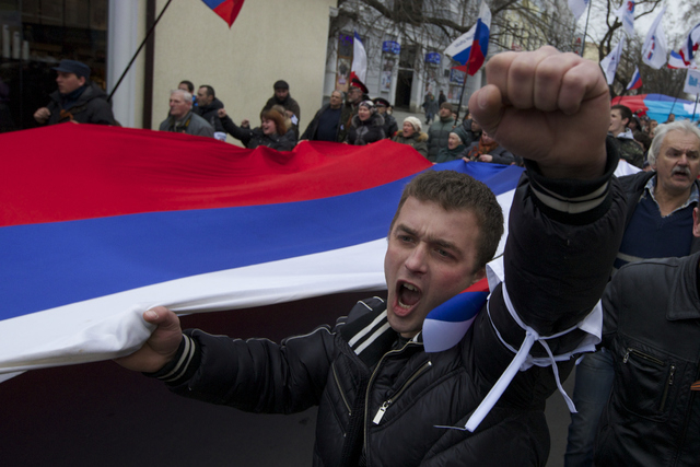 Local residents carry Russian flags and shout slogans rallying over the streets of Crimean capital Simferopol, Ukraine, on Saturday, March 1, 2014. Russian President Vladimir Putin asked parliamen ...