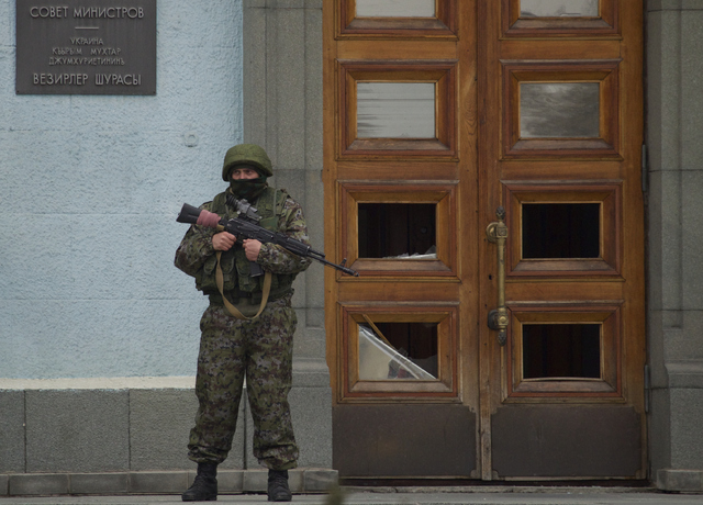 An unidentified man guards the entrance to a local government building in  Simferopol, Ukraine, on Saturday, March 1, 2014. Russian President Vladimir Putin asked parliament Saturday for permissio ...