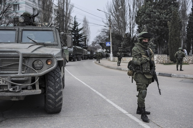 Troops in unmarked uniforms stand guard in Balaklava on the outskirts of Sevastopol, Ukraine, Saturday, March 1, 2014. An emblem on one of the vehicles and their number plates identify them as bel ...