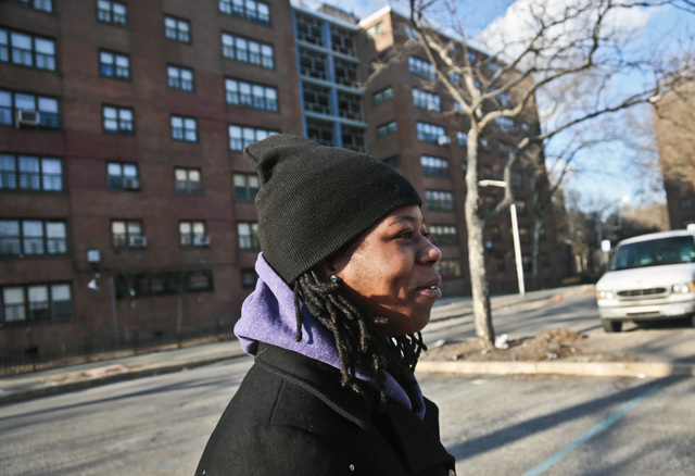 Naquasia LeGrand sits walks through a parking lot at the apartment complex where she lives in the Carnarsie section of Brooklyn, on Thursday Feb. 27, 2014 in New York.  A few months ago, LeGrand w ...