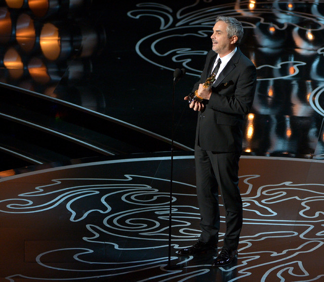 "Alfonso Cuaron accepts the award for best director of the year for ""Gravity"" during the Oscars on Sunday in Los Angeles.  (John Shearer/Invision/AP)"
