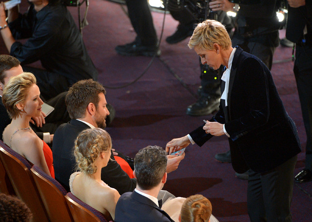 Ellen DeGeneres, right, gives Bradley Cooper a lottery ticket during the Oscars on Sunday in Los Angeles.  (John Shearer/Invision/AP)