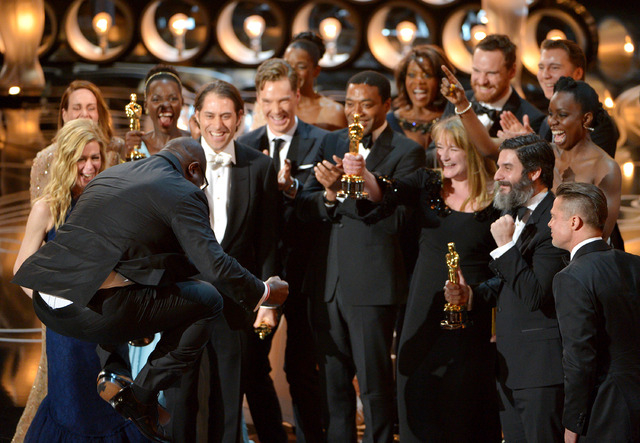 "Director Steve McQueen, left, celebrates with the cast and crew of ""12 Years a Slave"" as they accept the award for best picture during the Oscars on Sunday in Los Angeles. (John Shearer/Invision/AP)"