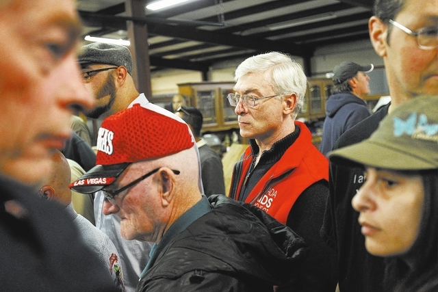 Dennis Dunn, in red vest, attends an auction at Nellis Auction in Las Vegas Saturday, Jan. 11, 2014. Dunn is the founder of Aids Project Nevada and he sells items at the auction to help fund the o ...