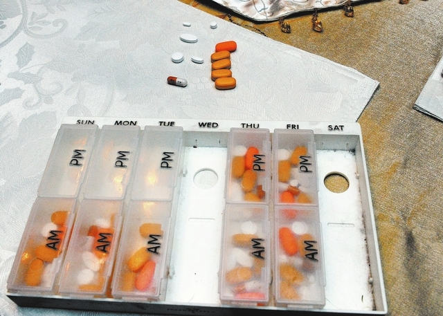 Dennis Dunn displays the pills he takes each day at his home in Las Vegas, Wednesday, Dec. 11, 2013. (Jerry Henkel/Las Vegas Review-Journal)