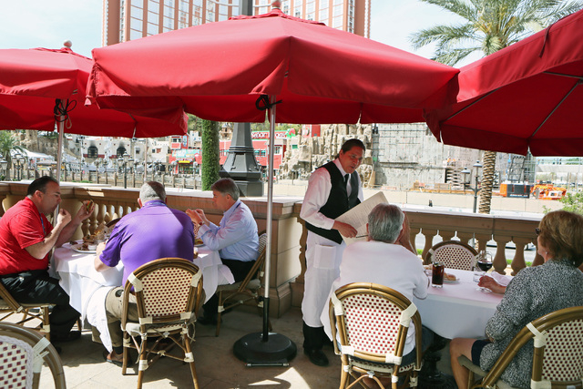 Carlos Escobar, center, waits on customers at Morels French Steakhouse & Bistro at the Palazzo on Thursday. Morels serves breakfast, lunch and dinner with indoor/outdoor dining options. (Ronda Chu ...