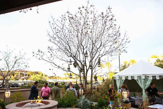 People mingle during a company event in the outdoor area at Vintner Grill, 10100 W. Charleston Blvd., in the Summerlin area on Thursday. (Chase Stevens/Las Vegas Review-Journal)