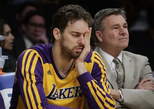 Los Angeles Lakers' Pau Gasol covers his face while sitting on the bench during Thursday night's game against the Los Angeles Clippers. The Clippers won 142-94. (AP Photo/Jae C. Hong)