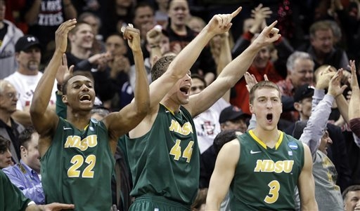 Players on the North Dakota State bench stand and cheer as their team takes the lead against Oklahoma in overtime during a second-round game of the NCAA men's college basketball tournament in Spok ...