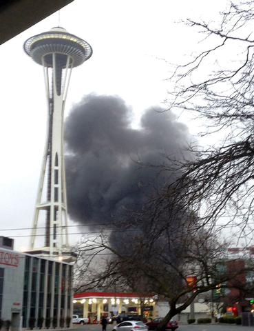Smoke rises at the scene of a helicopter crash outside the KOMO-TV studios near the Space Needle in Seattle on Tuesday. The station says the helicopter was apparently was lifting off from its roof ...