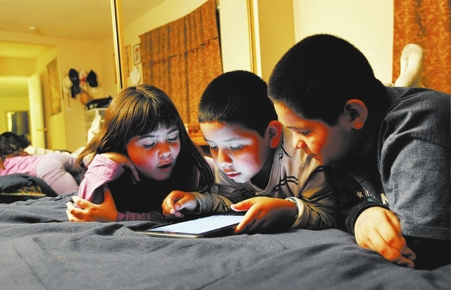 From left, friends Annakaren Villalobos, Anthony Ruiz, and Omar Calderon play a video game together in Ruiz's parent's room at his home in Las Vegas on Thursday, Feb. 27, 2014. All three children  ...