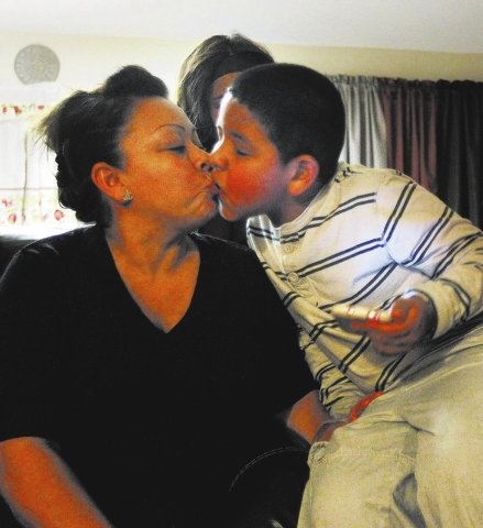 Julia Aguirre receives a kiss from her son Anthony Ruiz, who suffers from autism, while in their home in Las Vegas on Thursday, Feb. 27, 2014. Ruiz has been on a waiting list for a year to receive ...