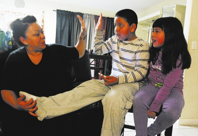 Julia Aguirre receives high five from her son Anthony Ruiz, who suffers from autism, while in their home in Las Vegas on Thursday, Feb. 27, 2014. Ruiz has been on a waiting list for a year to rece ...