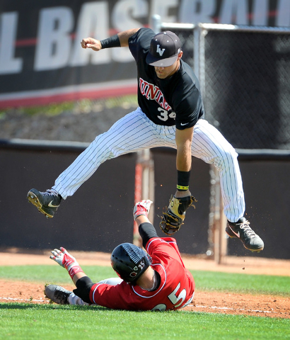 San Diego State's Ty France slide beneath UNLV first baseman Patrick Armstrong during a NCAA baseball game at Wilson Stadium on Sunday, March 23, 2014. France was initially called out, but it was  ...