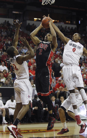 UNLV's Khem Birch tries to score in between San Diego State's Skylar Spencer (0) and Josh Davis (22) during their Mountain West basketball tournament semi-final game at the Thomas & Mack Center in ...
