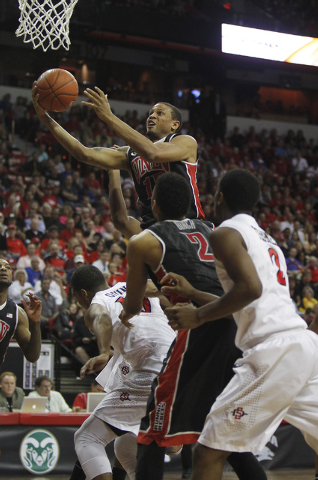 UNLV's Bryce Dejean-Jones (13) goes to the basket over San Diego State's Aqeel Quinn (10) during their Mountain West basketball tournament semi-final game at the Thomas & Mack Center in Las Vegas  ...