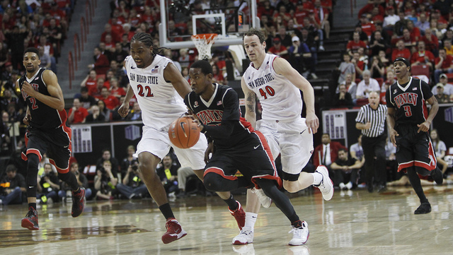 UNLV's Deville Smith (33) leads a fast break past San Diego State's Josh Davis (22) and Matt Shrigley (40) during their Mountain West basketball tournament semi-final game at the Thomas & Mack Cen ...