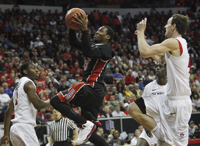 UNLV's Deville Smith (33) goes to the basket past San Diego State's Matt Shrigley (40), Xavier Thames (2) and Dwayne Polee (5) during their Mountain West basketball tournament semi-final game at t ...