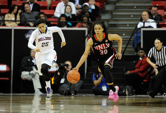 UNLV's Mia Bell (30) brings the ball up court against Fresno State's Moriah Faulk during the second half of an NCAA college basketball game in the Mountain West Conference women's tournament at th ...