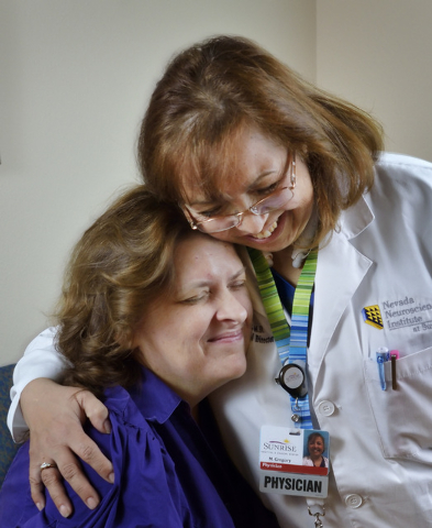 Dr. M. Gabriela Gregory, right, hugs patient Nancy Buckley after injecting her with Botox to help treat Buckley's migraine headaches at the Nevada Neurosciences Institute at 3131 La Canada St. in  ...