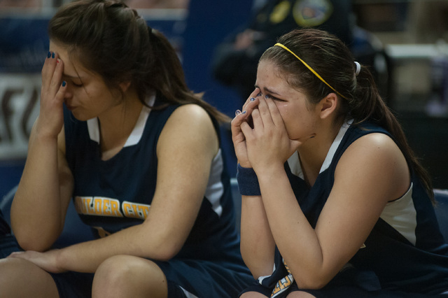 Boulder City's Katlyn Daly (4) cries next to Sariah Gneiting (32) in the final seconds against Lowry during the Division I-A state final on Saturday. Lowry defeated Boulder City 44-34. (Kevin Clif ...