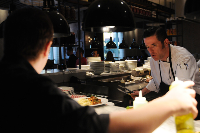 Christian Gonzalez-Borda, right, sous chef at Buddy V's Ristorante at The Venetian casino-hotel in Las Vegas, sets a plate on the counter during dinner service Saturday, March 22, 2014. (Er ...