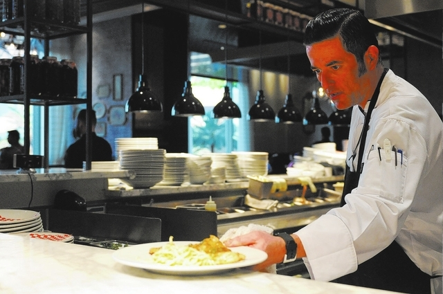 Christian Gonzalez-Borda, sous chef at Buddy V's Ristorante at The Venetian casino-hotel in Las Vegas, sets a plate on the counter during dinner service Saturday, March 22, 2014. (Erik Verd ...