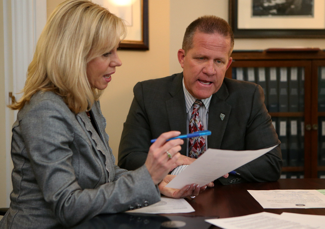 Shelly Capurro, an elections division officer with the Secretary of State's office, processes paperwork with State Sen. Mark Huchison, R-Las Vegas, as he files to run for Lt. Governor in Carson Ci ...