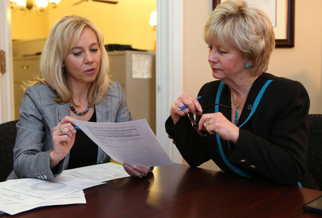 Shelly Capurro, an elections division officer with the Secretary of State's office, processes candidate paperwork with Controller Kim Wallin who is running for state treasurer in Carson City, Nev. ...